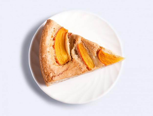 Uma fatia de torta de caqui doce isolada no branco
