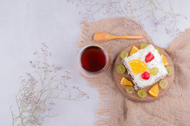 Uma fatia quadrada de bolo de frutas com um copo de chá.