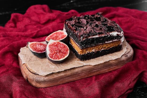 Uma fatia quadrada de cheesecake de chocolate em uma placa de madeira.