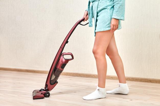 Uma faxineira de robe azul está passando o aspirador em uma sala vazia com piso laminado usando aspirador de mão sem fio.