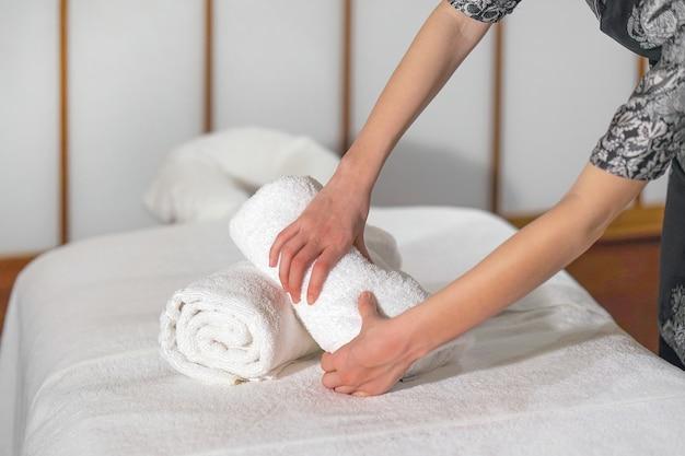Uma faxineira dobra uma toalha em uma cama de massagem.