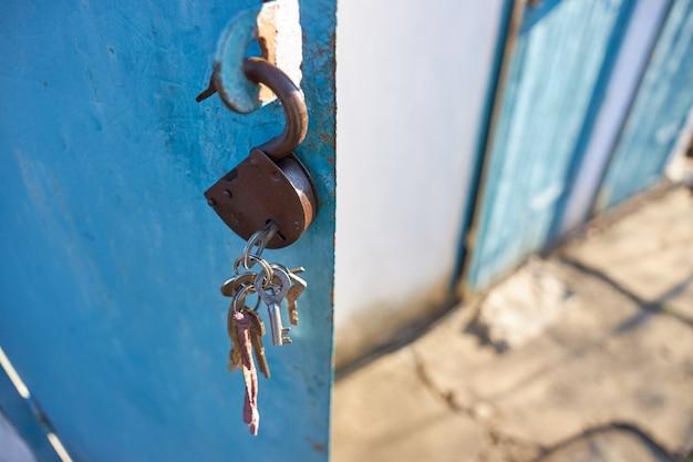 Uma fechadura com um molho de chaves pendurada em uma porta de metal aberta