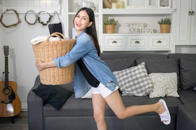 Uma feliz dona de casa está carregando panos de balde para lavar na casa.