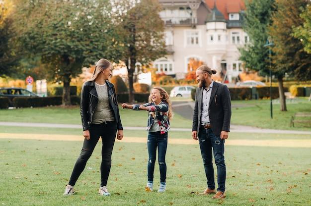 Uma feliz família de três pessoas corre pela grama na cidade velha da áustria.