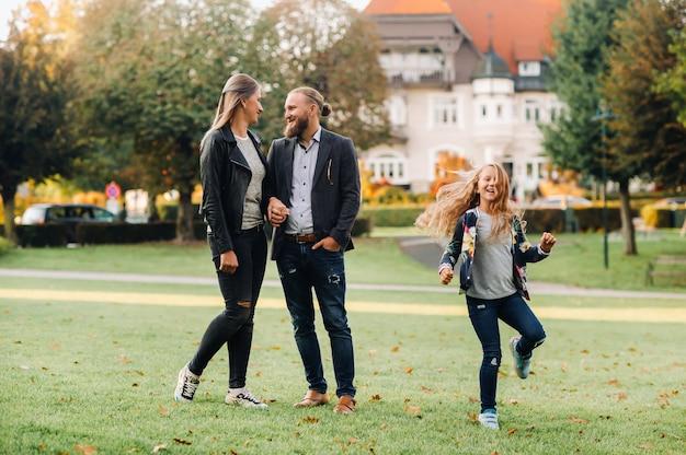 Uma feliz família de três pessoas corre pela grama no centro histórico da áustria
