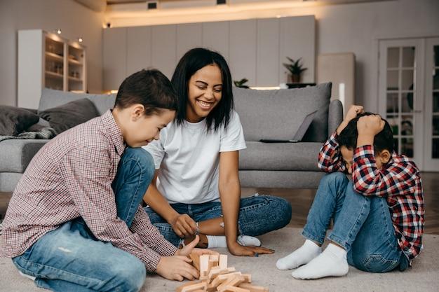 Uma feliz família negra, mãe e dois filhos brincando com uma rodada de jenga