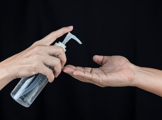 Uma fêmea com um desinfetante para as mãos empurra o gel para a mão masculina.