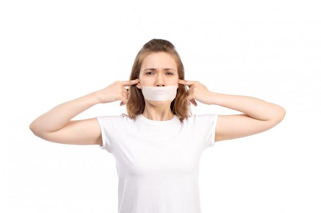 Uma fêmea jovem vista frontal em t-shirt branca com bandagem branca em volta da boca, fechando os ouvidos no branco