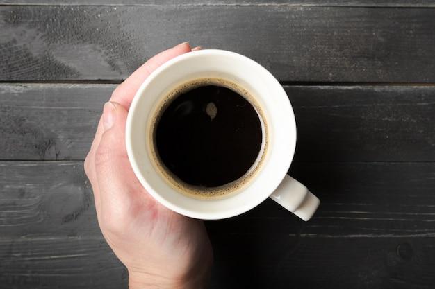 Uma fêmea mãos segurar uma xícara de café na mesa de madeira