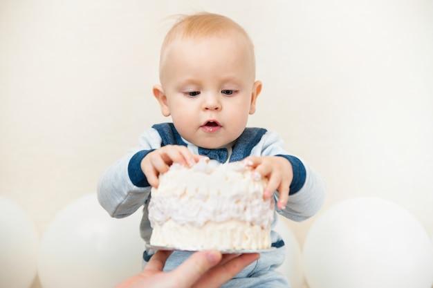Uma festa de aniversário de bebê ano. bebê comendo bolo de aniversário close-up