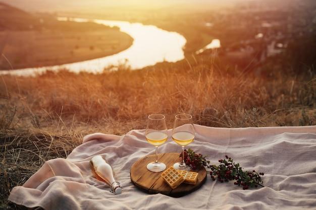 Uma festa na montanha ao pôr do sol com vinho. noite romântica no verão. piquenique.