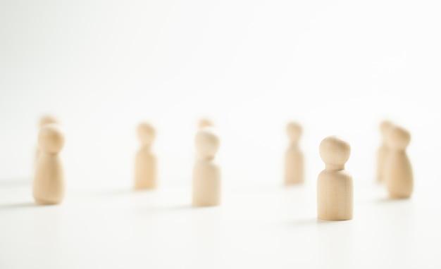 Uma figura de madeira em pé com uma equipe para influenciar e fortalecer. conceito de liderança, vencedor de competição de sucesso e líder com influência e distanciamento social para um novo estilo de vida normal