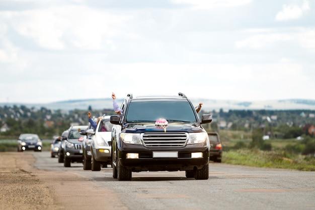 Uma fila de carros decorados para um casamento
