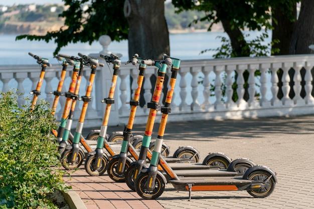 Uma fila de scooters estacionadas na calçada da cidade, veículo elétrico