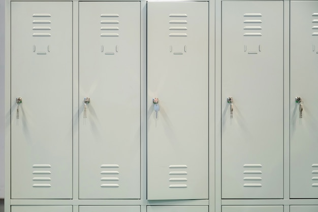 Uma fileira de armários escolares de metal cinza com chaves nas portas.