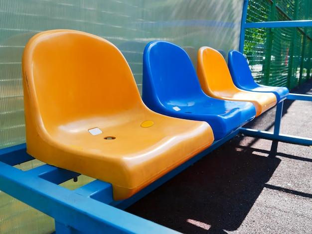 Uma fileira de assentos de plástico para esperar na quadra de tênis.