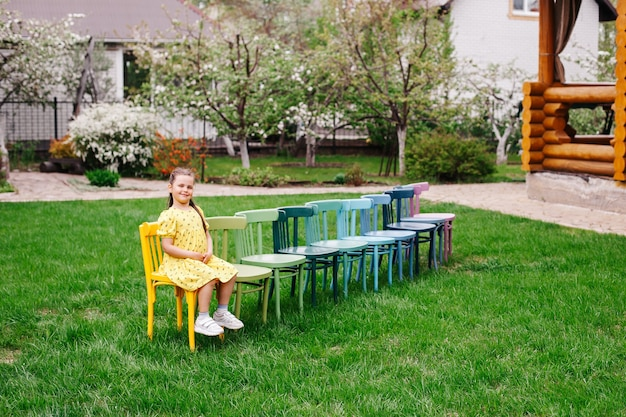 Uma fileira de cadeiras de madeira no gramado do quintal para férias em família em um jardim florido de primavera