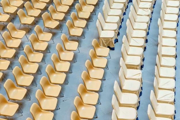 Uma fileira de cadeiras de plástico amarelas, cadeiras reclináveis em estádios de palco sem pessoas