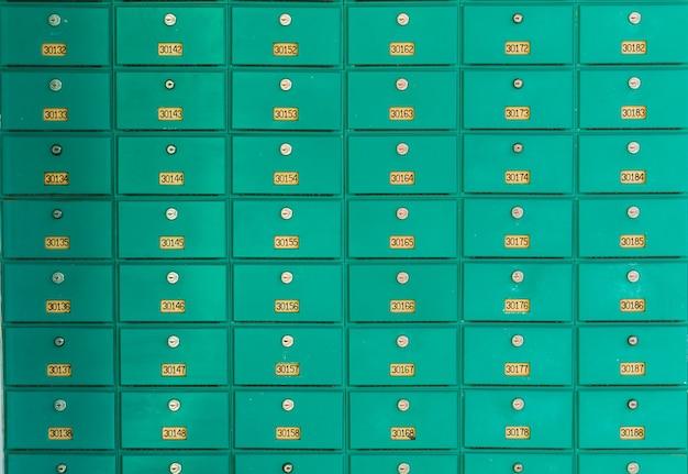 Uma fileira de caixas de correio verdes. correios