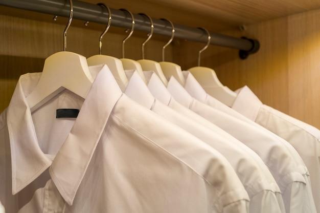 Uma fileira de camisas masculinas brancas simetricamente penduradas