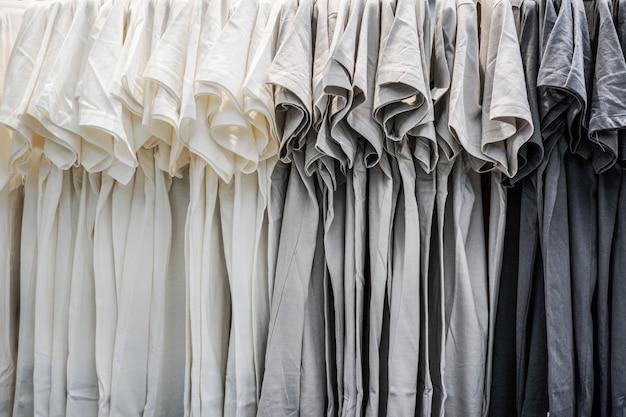 Uma fileira de camiseta pendurada na prateleira