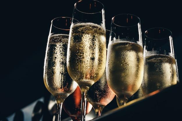 Uma fileira de copos cheios de champanhe está alinhada pronta para ser