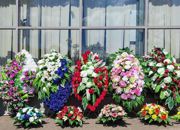 Uma fileira de coroas para o enterro as coroas fúnebres são feitas de flores de plástico coroas artificiais