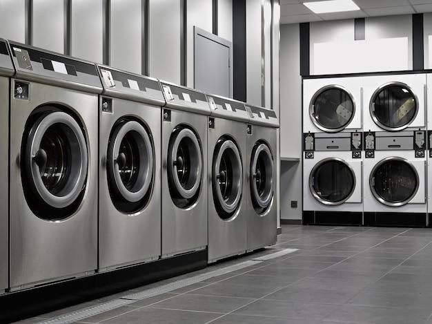 Uma fileira de máquinas de lavar industriais em uma lavanderia pública