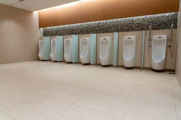 Uma fileira de mictórios brancos em uma parede de azulejos em um banheiro público