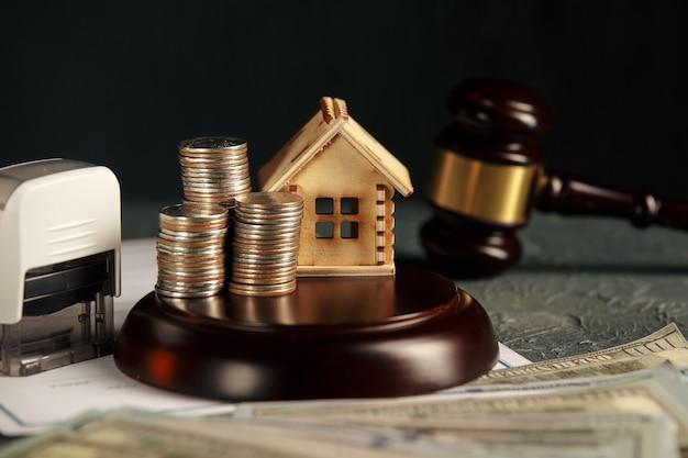 Uma fileira de moedas em um modelo de casa pequena e um martelo de leilão de lei