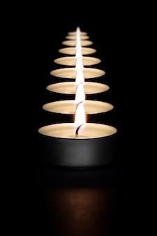 Uma fileira de velas acesas em um fundo escuro com um sinalizador em primeiro plano. layout, maquete.