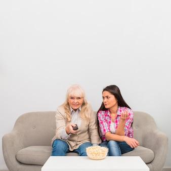 Uma filha com raiva olhando para sua mãe sênior, mudando o canal com o controle remoto