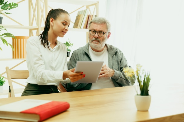 Uma filha ou neta passa tempo com o avô ou o homem mais velho. família ou dia dos pais, emoções e felicidade. retrato do estilo de vida em casa. menina cuidando do pai. usando um tablet.