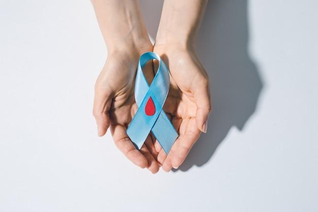 Uma fita azul com uma gota de sangue simboliza o diabetes.