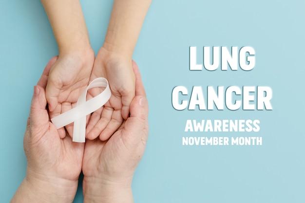 Uma fita branca nas mãos de uma criança e uma mãe conceito de conscientização do câncer de pulmão mês de novembro