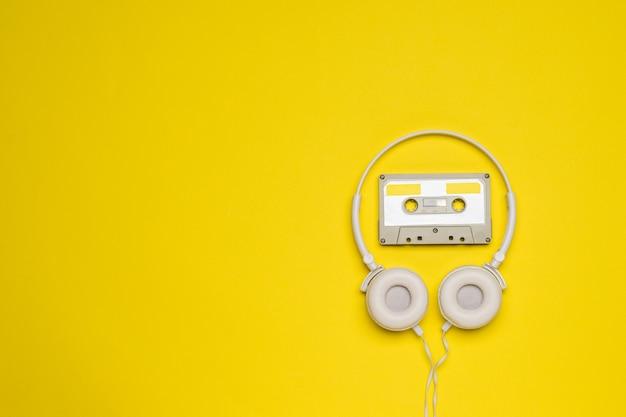 Uma fita cassete cinza com fita magnética e fones de ouvido brancos em um fundo amarelo.