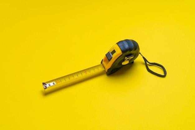 Uma fita métrica isolada, conceito de construção, instrumento métrico simples