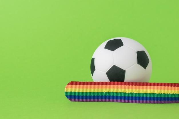 Uma fita nas cores lgbt e uma bola de futebol sobre um fundo verde. o conceito de lgbt no futebol.