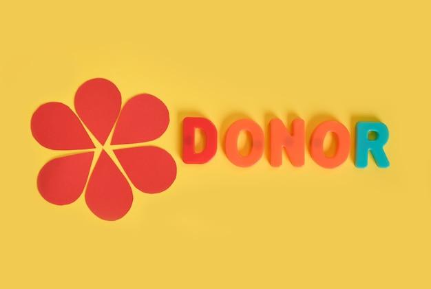 Uma flor feita de papel, gotas de sangue e a inscrição do doador de letras de plástico em um amarelo