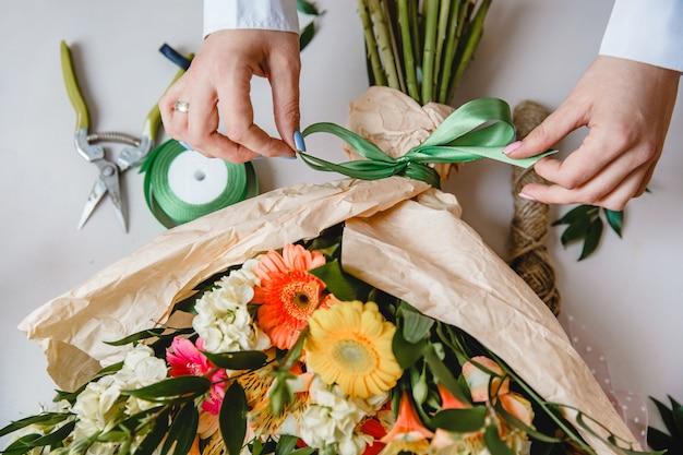 Uma florista amarra um laço de fita em um buquê de flores embrulhado em papel artesanal na mesa