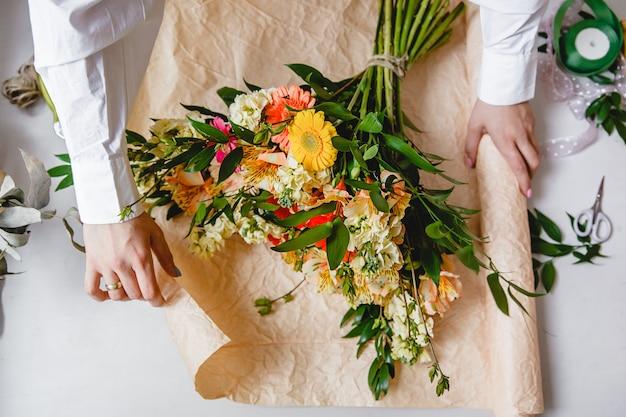 Uma florista de camisa branca embrulha um buquê de flores frescas em papel