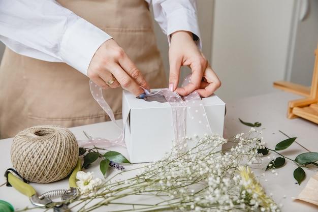Uma florista decora uma caixa de presente com flores e uma fita em uma mesa branca, apenas as mãos estão na moldura