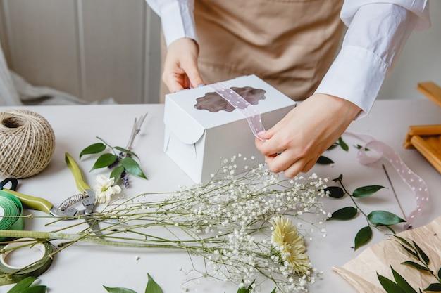 Uma florista decora uma caixa de presente com flores e uma fita em uma mesa branca