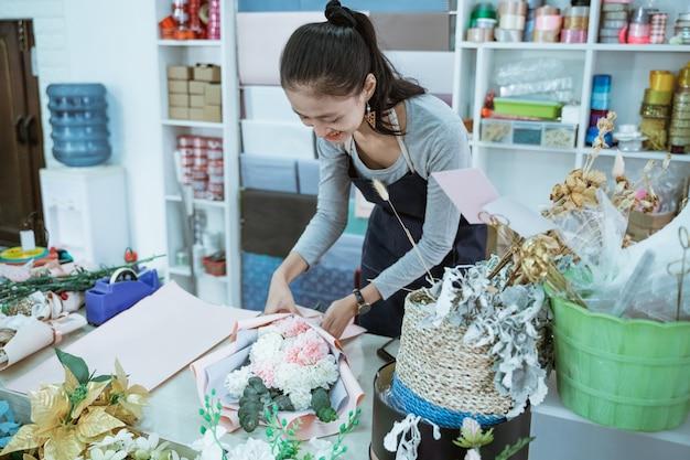 Uma florista sorridente trabalhando em uma loja de flores faz um pedido de flores de flanela em uma mesa de trabalho
