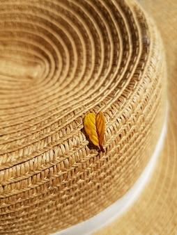 Uma folha amarela caída de uma árvore encontra-se em um chapéu de palha. conceito de outono, acessórios.