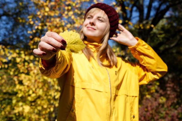 Uma folha amarela de outono na mão de uma mulher desfocada no contexto das folhas de outono. fechar-se