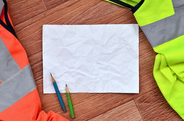 Uma folha amassada de papel com dois lápis rodeados por uniformes de trabalho verdes e laranja