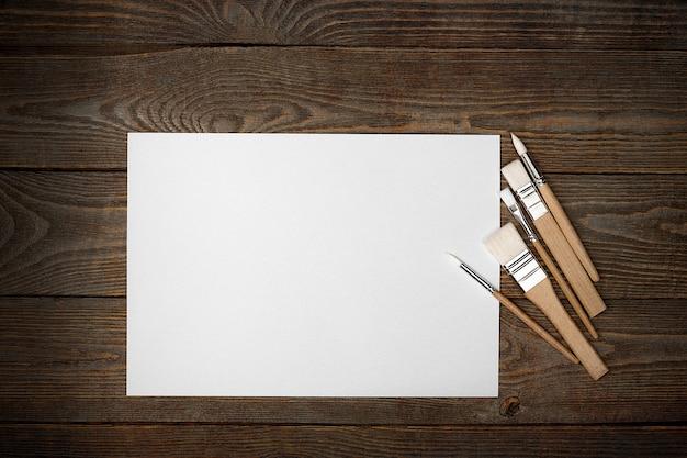 Uma folha branca limpa e pincéis em um fundo de textura de madeira com espaço para copiar.