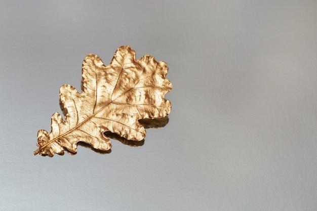 Uma folha de carvalho pintada de cor dourada sobre fundo prateado. decoração de design com folha de outono e seu reflexo. vista superior e copie o espaço.