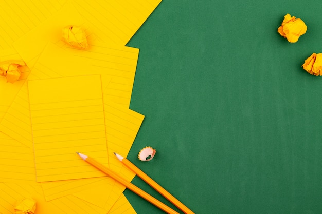 Uma folha de papel alaranjada encontra-se em uma placa de escola verde que constitui um frame para o texto. perto de lápis e páginas amarrotadas. copie o espaço plano de configuração vista superior conceito de educação.